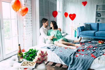 Bottle of champagne, bouquet of roses and box of chocolate candies are lying on the table on beautiful kissing couple background.