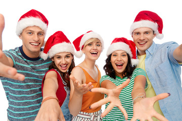 christmas, holidays and friendship concept - group of happy smiling friends in santa hats having fun over white background