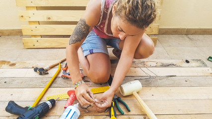 woman working outdoor with hardware stuffs building furniture or something for home with recycled pallets pine wood. do it yourself hobby concept Wall mural