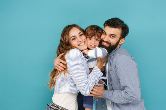 A happy family on blue studio background. The father, mother and son posing together