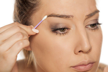 Young woman contouring her eyebrows with cotton swab on white background