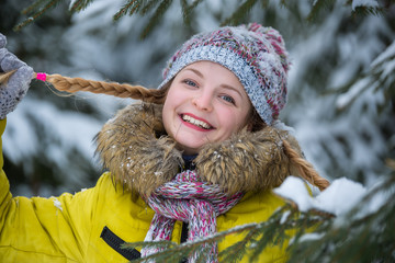 Portrait of girl in a hat and warm jacket in the forest who have fun with snow