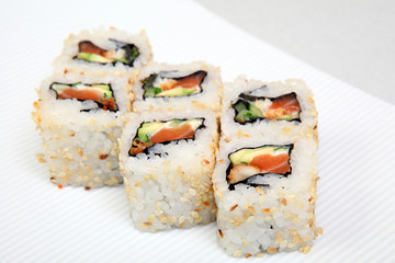Roll California in sesame. Sushi with crab, eel, cucumber. Japanese food on a beautiful dish.