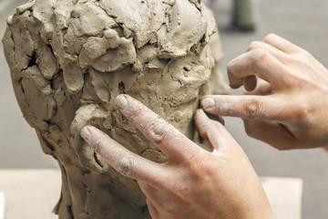 sculptor creates a bust and puts his hands clay on the skeleton of the sculpture. Close-up Fototapete