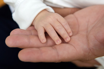 The hand of a newborn child in his father's hand. The tenderness of motherhood is in the details. Procreation in childbirth and love.