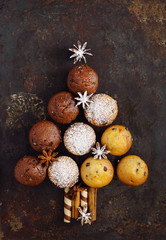 Assorted muffins in the shape of a Christmas tree on the old black rusty metal background. Top view.