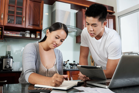 Young married couple writing down expenses into notepad