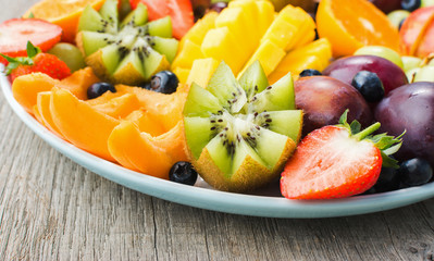 Assorted fruits and berries platter, strawberries blueberries, mango orange, apple, grapes, kiwis on the grey wood background, copy space for text, selective focus