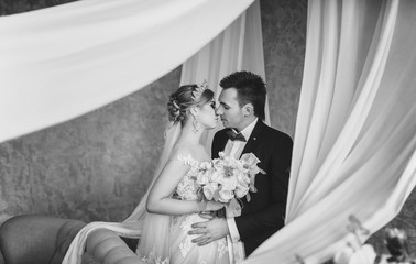 Kiss of the newlyweds. Enamored bride and groom. Gray interior. Black and white photography. Monochrome.