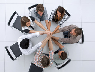 top view.the smiling business team folded their hands together
