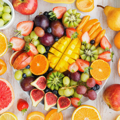 Variety of cut fruits and berries platter, strawberries blueberries, mango orange, apple, grapes, kiwis on the white wood background, copy space for text, square, top view, selective focus