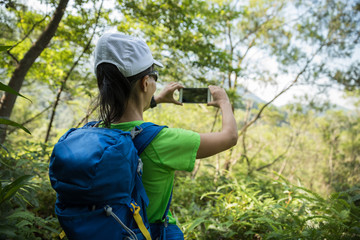 Backpacker taking picture with smartphone in sunny tropical rainforest