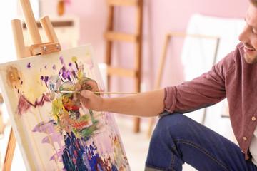 Male artist painting in workshop