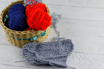 Wicker basket with colorful knitting yarns, knitting needles and knitting on white wooden table