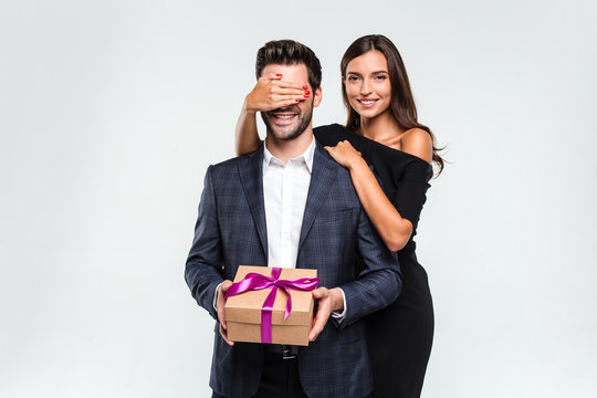 Just don't look a minute! Young handsome men holding a gift box while his girlfriend covering his eyes with her hand and looking at camera with smile