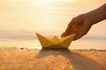 Woman putting origami boat on water surface near bank