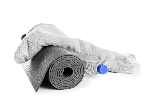 Yoga mat, bottle of water and soft towel on white background