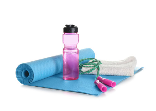 Yoga mat with towel, jumping rope and bottle of water on white background