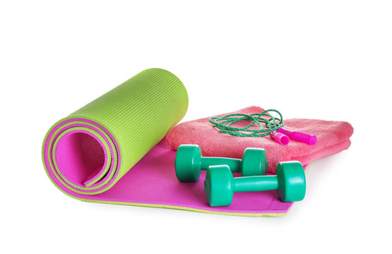 Yoga mat with dumbbells, jumping rope and towel on white background