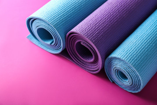 Different yoga mats on color background