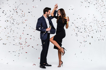 Pure celebration! Full length of young beautiful couple bonding and dancing while standing against white background with confetti