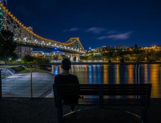 Human on bench watching at road bridge at night