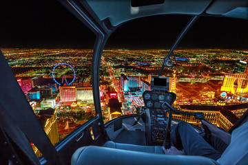 Garden Poster Las Vegas Helicopter interior on Las Vegas buildings and skyscrapers of downtown with illuminated casino hotels at night. Scenic flight above Vegas skyline by night in the Nevada United States of America.