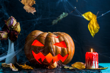 Halloween picture of table with pumpkin, burning candle,