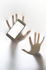 Silhouetted hands with mobile phone