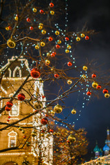 Photo of tree with golden and red balls on background of building