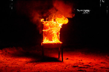 Wooden chair is on fire. Incineration of furniture. Conceptual photo, burnout Wall mural