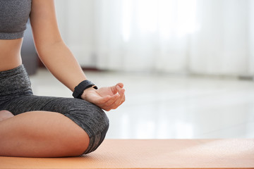 Crop shot of slim woman in sportswear and smart watch sitting on mat and meditating at home