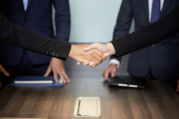 Faceless shot of formal businesspeople shaking hands above table in conference hall having meeting