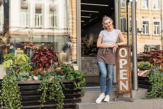 smiling attractive florist standing on stairs of flower shop and leaning on open sign