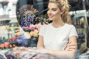 view through window of beautiful florist standing with crossed arms in flower shop and looking away