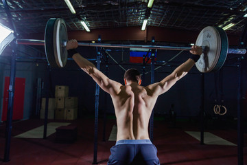 Portrait of a handsome athlete from behind. Athlete raises the barbell over your head. Studio shots in the dark tone. Cross style fit, deadlift