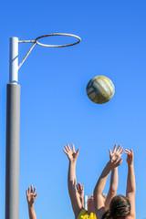 Netballers jumping for ball against blue sky