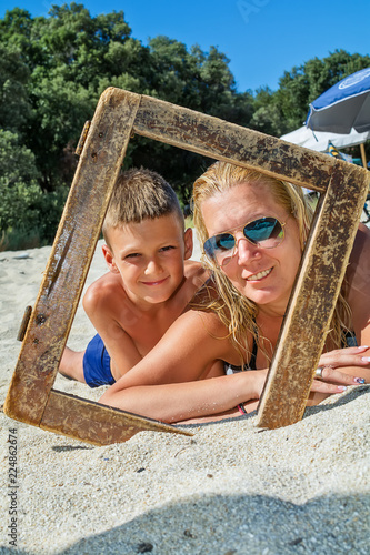 Mother And Son On Beach With Wooden Picture Frame Stock Photo And
