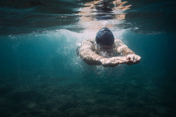 Swimmer dive in underwater. Underwater view of male athlete swimming