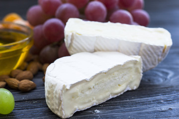 Cheese cuts with figs, nuts, honey, grapes on a dark rustic wooden boards background