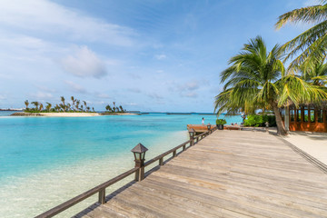 Amazing island in the Maldives ,Beautiful turquoise waters and white sandy beach with  blue sky  background for holiday vacation .