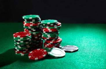 A stack of poker chips on green velvet casino table.