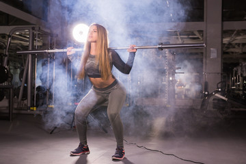sport, fitness, training and happiness concept - sporty woman with barbell in gym