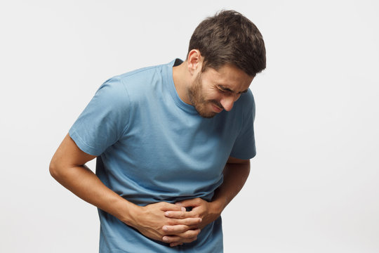 Young man touching his stomach isolated on gray background space. Abdominal pain or ache concept