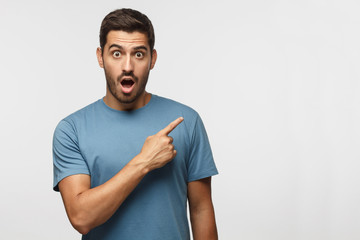 Young surprised man in blue t-shirt pointing right with his finger, shouting WOW, isolated on gray background with copy space fot your text. Shock content