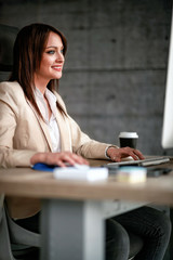 Smiling designer using computer in office