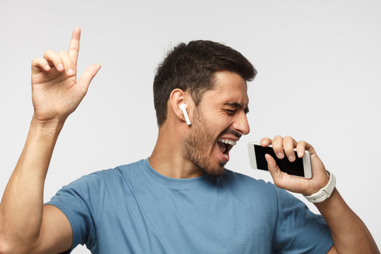 Young handsome man singing his favorite song, using his phone instead microphone, wearing blue t shirt and wireless earphones, pointing up, in the air with index finger