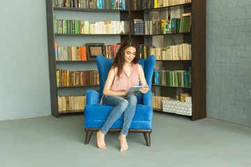 Technologies, people concept - young girl sitting on a chair and watching the tablet or surfing the net near the bookshelf