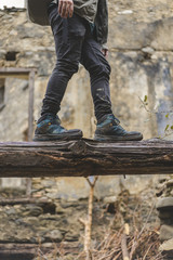 Man balancing on dead wood, partial view