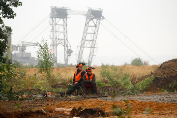 Two lumberjacks of German utility and power supplier RWE rest on a tree stump as a brown coal excavator of the Hambach open cast brown coal mining of RWE is seen behind them, near Kerpen-Buir